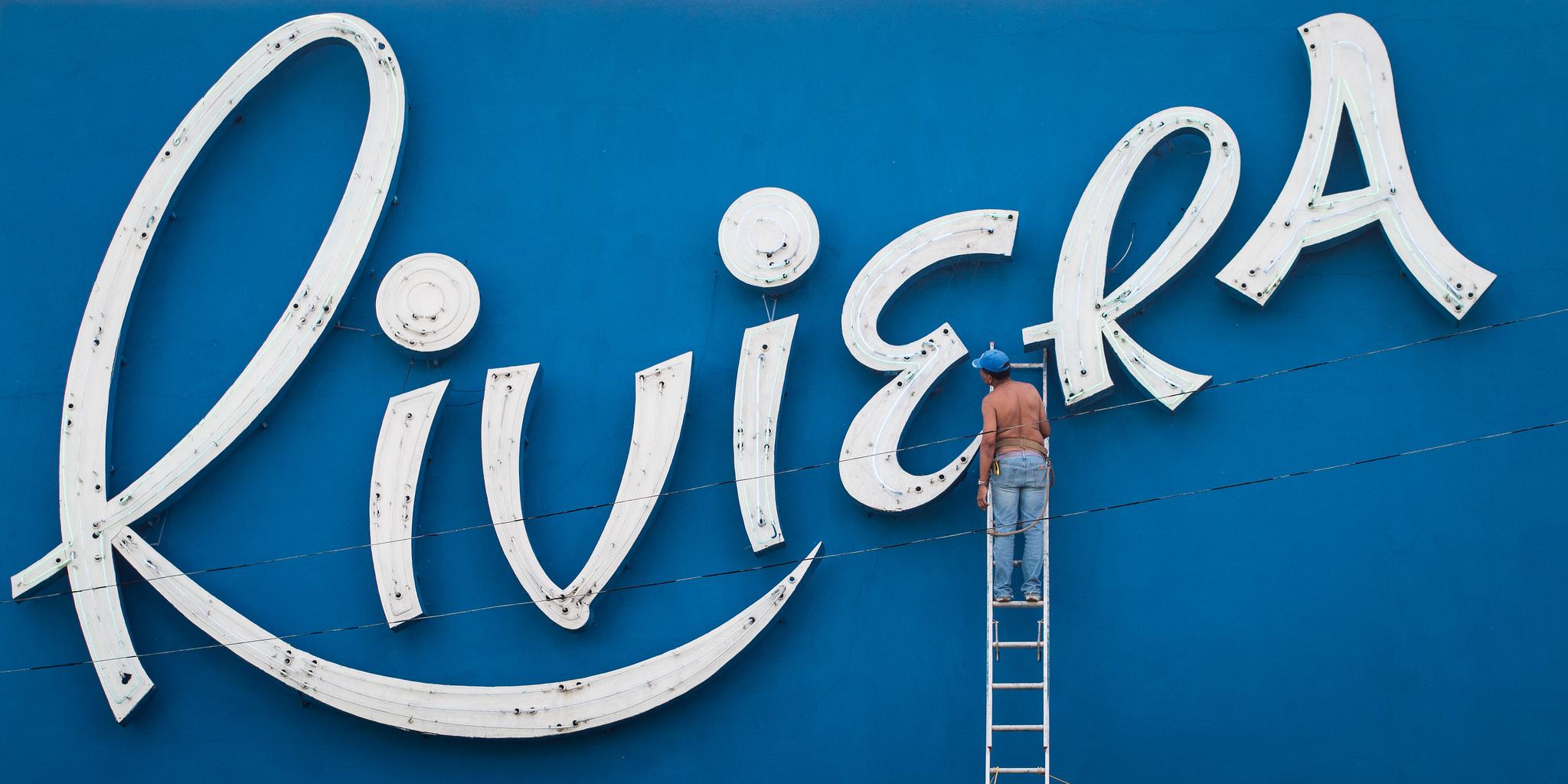 Straßenfotografie: Mann auf Leiter vor weißer Riviera-Leuchtreklame auf blauem Hintergrund