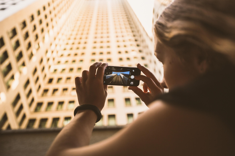 Hochhaus wird von junger Frau mit dem Smartphone fotografiert.