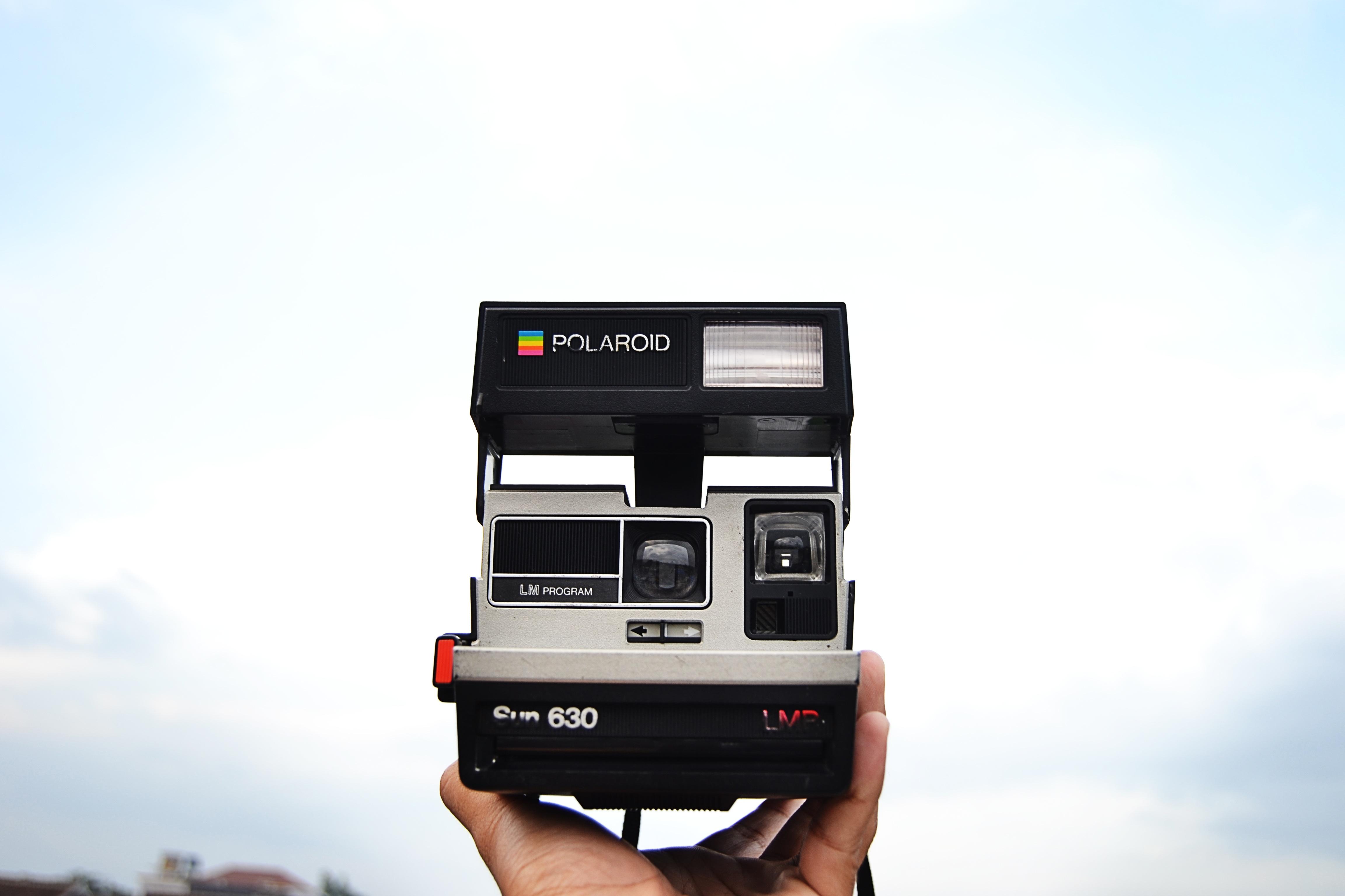 Eine Polaroid-Kamera, in den Himmel gehalten