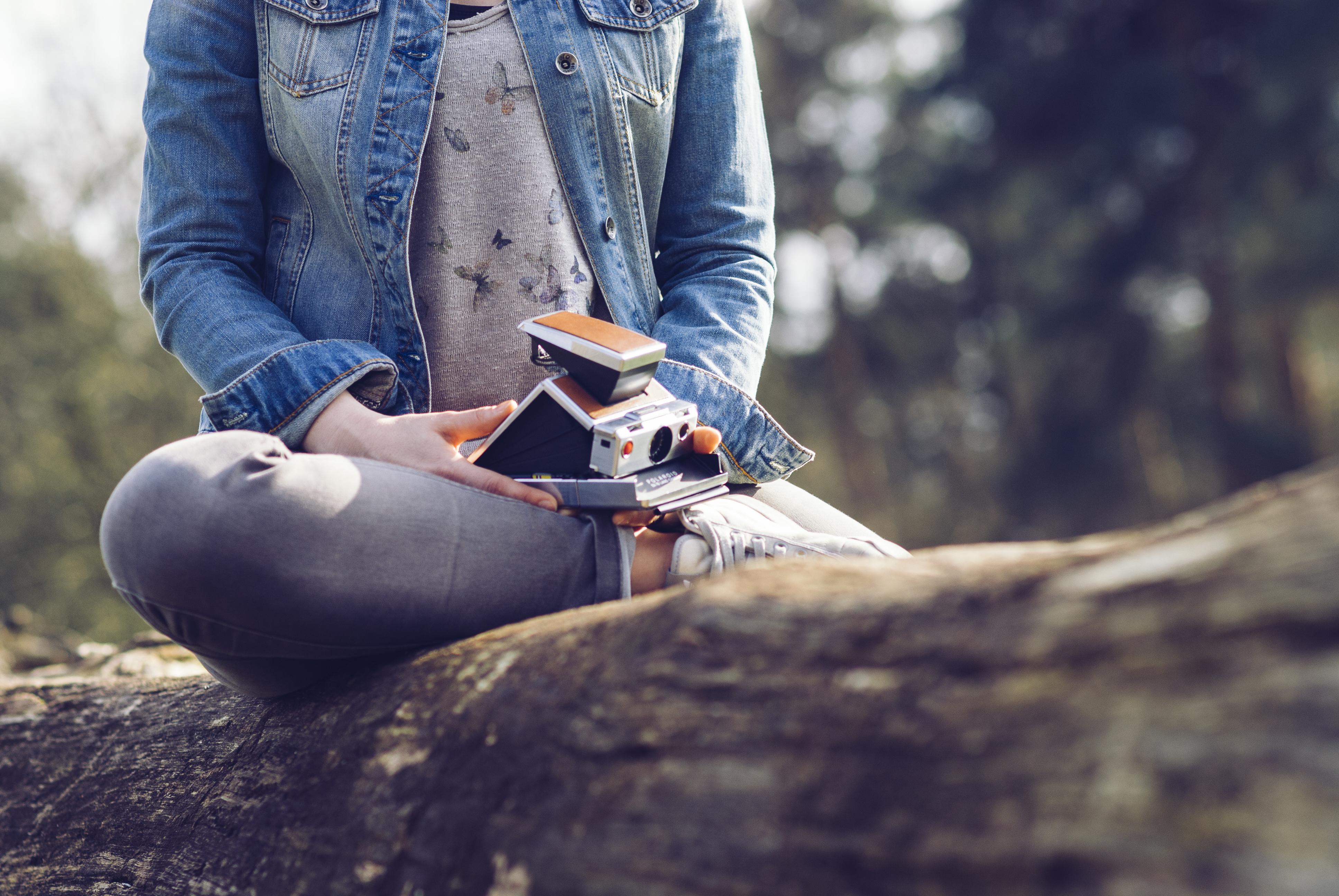Mädchen hält eine Polaroidkamera in den Händen