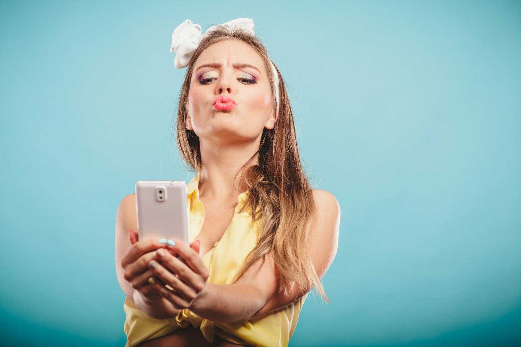 Mädchen mit Schleife im Haar macht ein Kussmund-Selfie