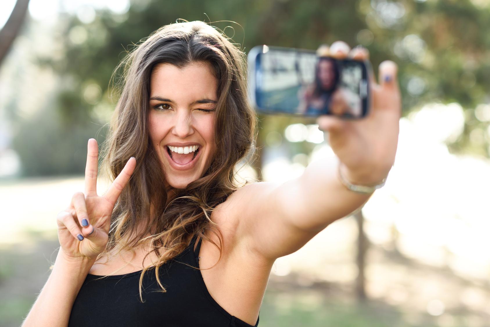 Mädchen macht für ein Selfie das Victory-Zeichen