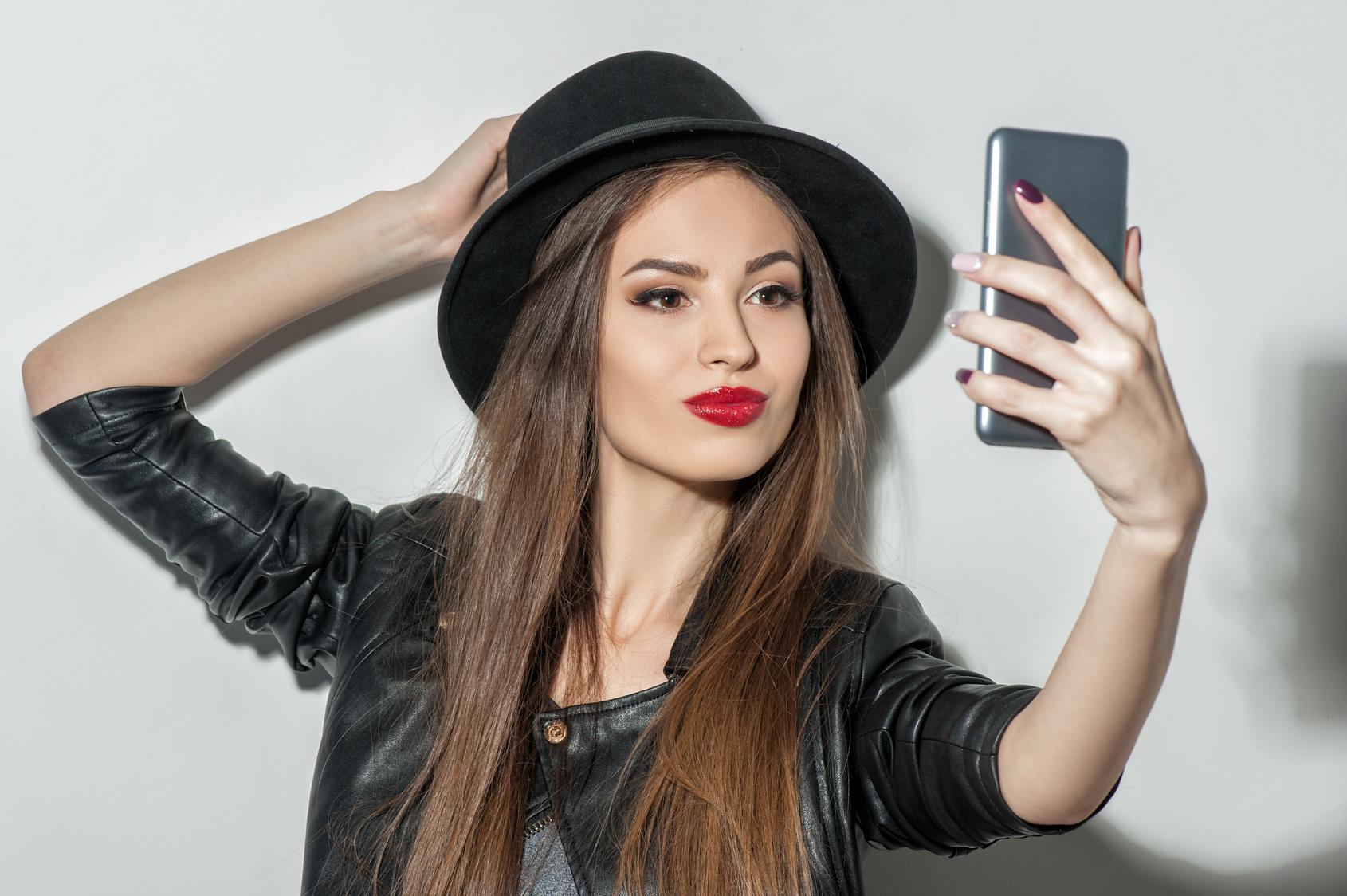 Mädchen mit Hut macht ein Smartphone-Selfie