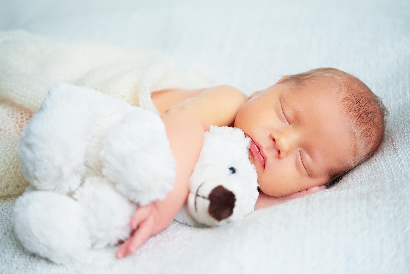 Schlafendes Baby auf weißem Laken mit weißem Stoffbären im Arm