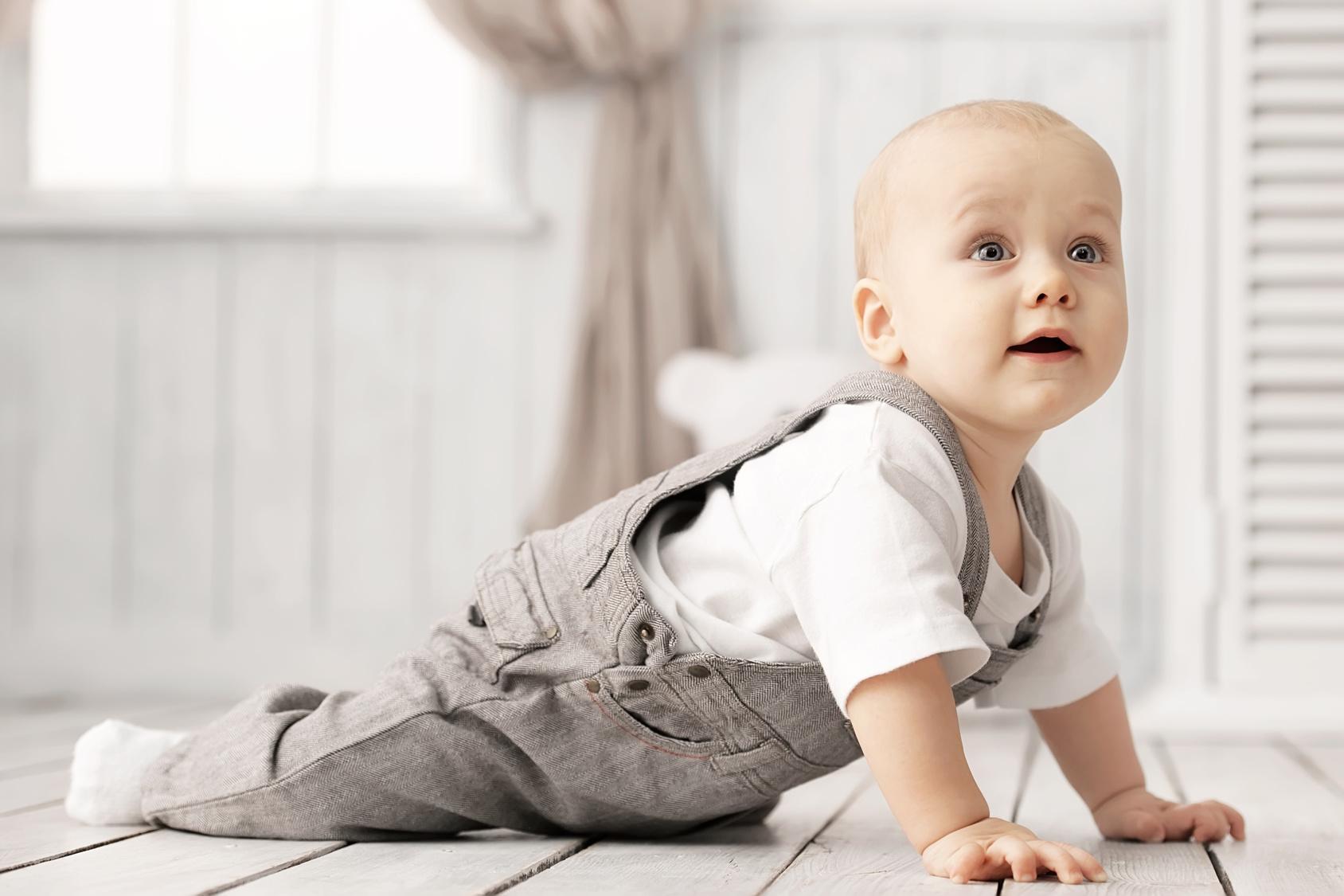 Baby in grauer Latzhose im Liegestütz. Ein fröhlich-aufmerksamer Blick geht nach oben.