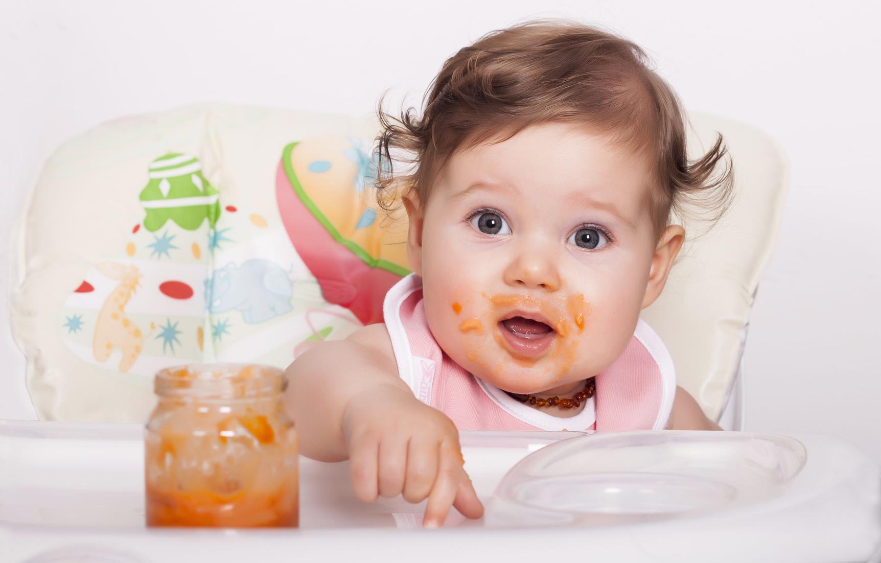 Baby im Kindersitz, mit großen Augen und geöffnetem Mund, der mit Brei verschmiert ist.