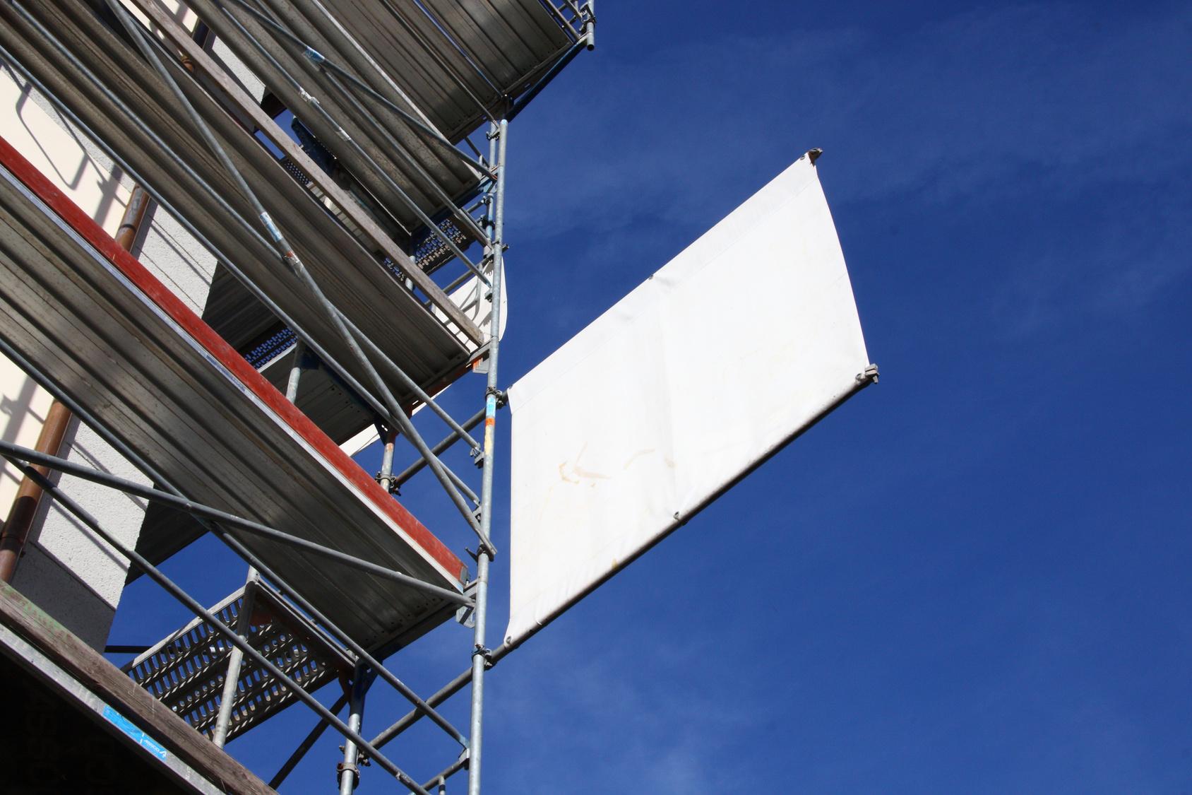 Eine weiße PVC-Plane, an ein Baugerüst gespannt.