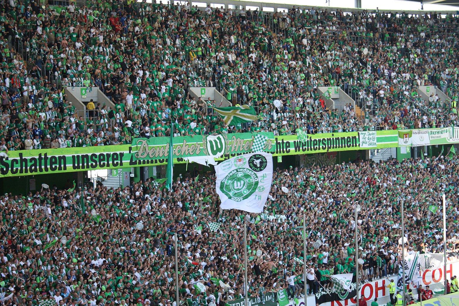 Fanblock des VfL Wolfsburg mit Bannern und Fahnen.