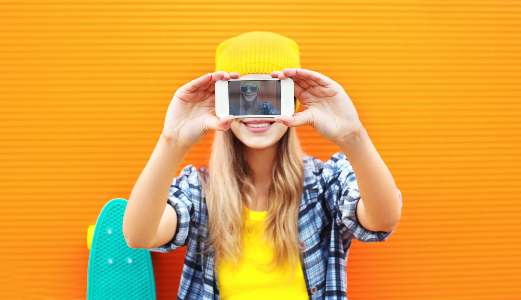 Junge Frau nimmt dem Smartphone ein Selfie auf