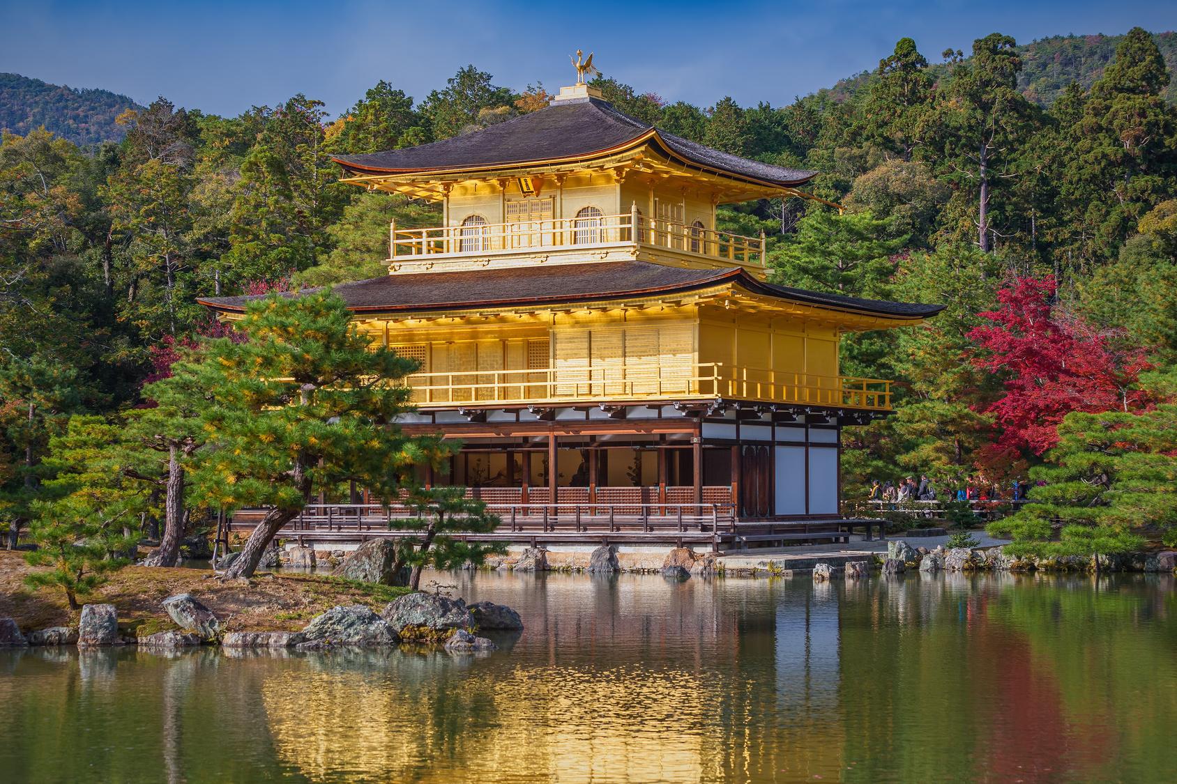 Der mit Blattgold versehene Goldene Pavillon in Kyoto glänzt im Sonnenlicht. Ein Wald erhebt sich im Hintergrund; im Vordergrund glitzert das Wasser eines Sees.