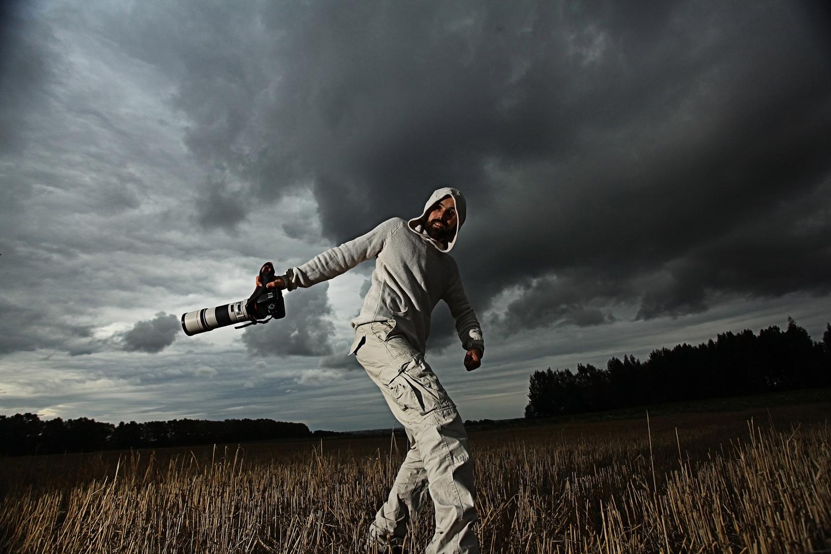 Ein Mann hält unter dunkelgrauen Wolken eine Kamera mit großem Teleobjektiv in der rechten Hand.