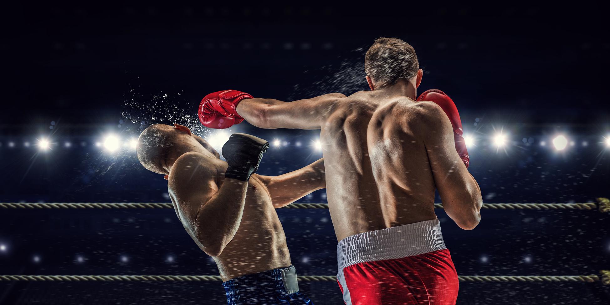Zwei Boxer im Ring. Ringsum Scheinwerferlicht. Der Boxer im Vordergrund setzt eine linke Gerade gegen den Kopf seines Gegners.