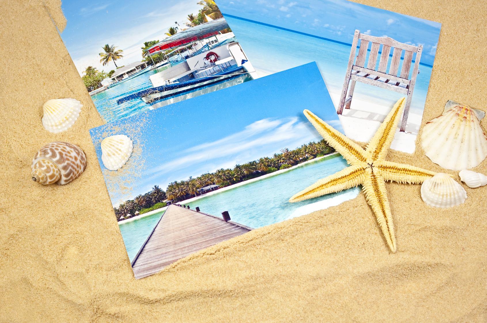 Fotos von tropischer Strandkulisse im Sand mit Muscheln und Seestern dekoriert.
